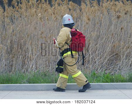 A fireman with a knapsack goes somewhere