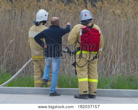 Two firefighters and a man showing somewhere