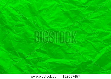 Background of crumpled green paper. Wrinkled paper close-up