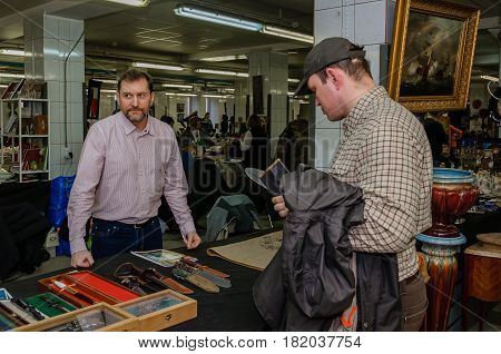 Moscow, Russia - March 19, 2017: Seller of antique knives, daggers and guns behind the counter with a weapon at the fair