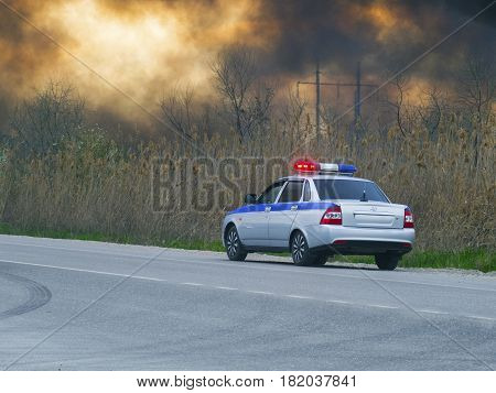 A police car by the roadside. The sky is in the smoke.