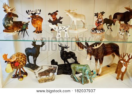 MOSCOW, RUSSIA - OCT 28, 2016: Many different figurines of elk by Verbilki Porcelain Factory inside glass box at private collection.