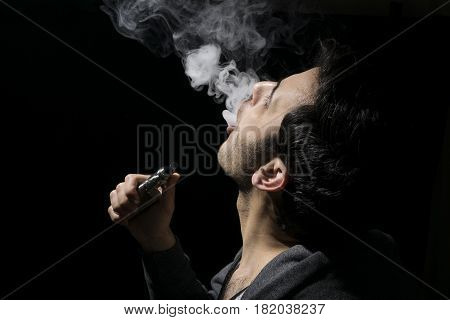 Isolated Young Man Vaping An E-cig Or Electronic Cigarette Holding A Mod.