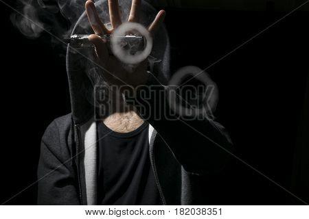 Young Man Doing Vaping Tricks Two Circles.