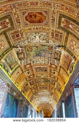 Vatican City - June 25 2015: Beautiful decorated painted ceiling with different scenes and carvings on a long lit hallway in the Vatican Museum