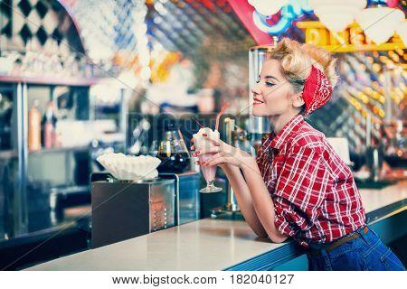 Pin-up girl with milkshake indoors