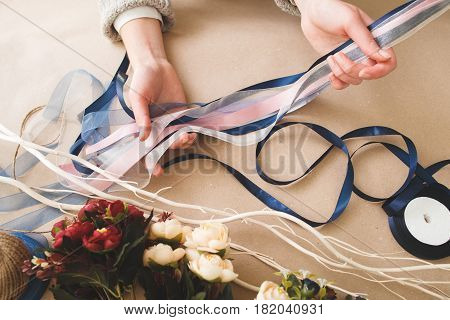 Floral decoration, beautiful creative handmade art, craftsmanship. Unrecognizable person holding colorful ribbons and artificial flowers on beige background, top view.