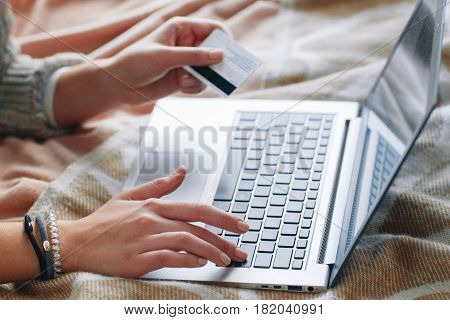 Unrecognizable woman with credit card on laptop, close up. Internet safe payments, security and protection, online shopping and money transferring concept.