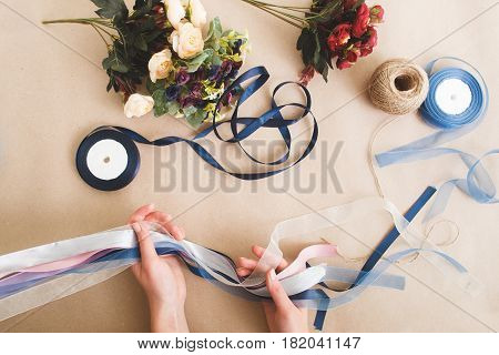 Unrecognizable person make decorations from colorful artificial flowers and ribbons on beige background, flat lay. Craftsmanship, diy art, creative hobby concept.