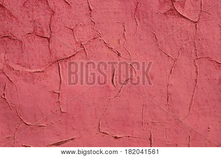 Old shelled and cracked red painted wall in sunlight as a background