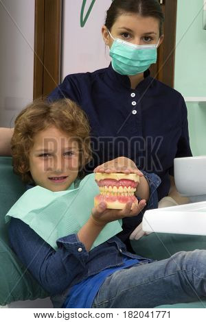 Kid showing the perfect smile at dentist studio.