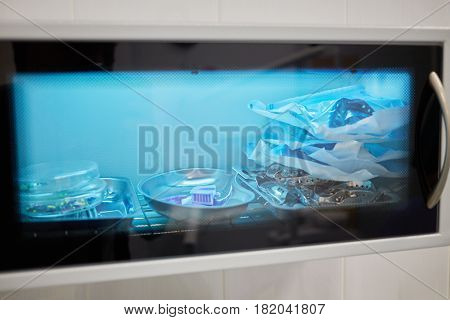 Closeup different instruments and accessories inside ultraviolt sterilizer.