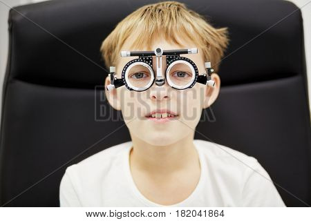 Portrait of boy in ophthalmic glasses sitting in armchair.