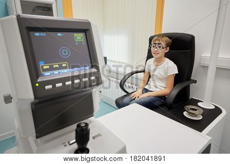 Boy in ophthalmic glasses sits in armchair in medical room.