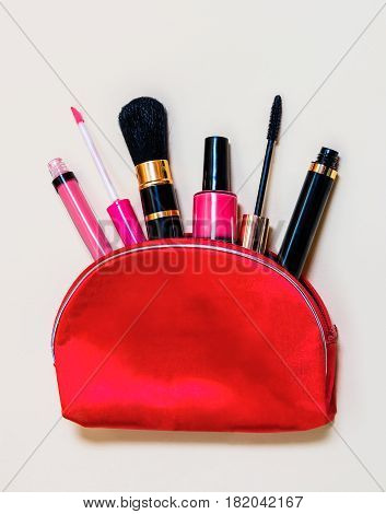 Makeup bag with cosmetic products spilling out to beige background