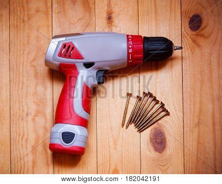 Screw gun or electric screwdriver on wooden background with screw