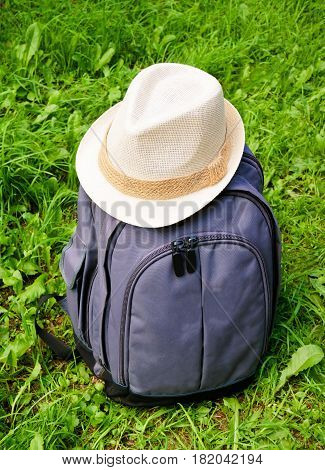 Gray backpack with white hat on grass