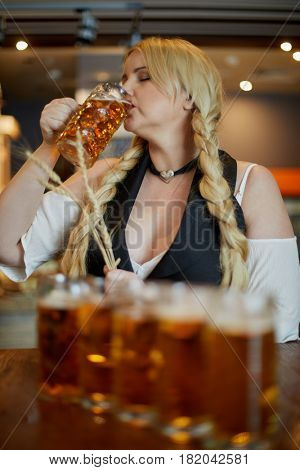 Blonde woman stands holding spikelets in hand and drinking beer at bar counter in cafe.