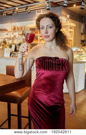 Smiling woman in red slinky evening dress with glass of beverage at bar counter.