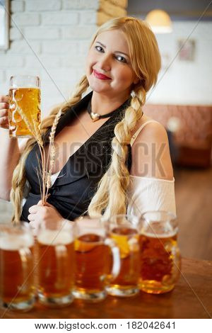 Smiling blonde woman stands holding spikelets in one hand and mug of beer in another at bar counter in cafe.