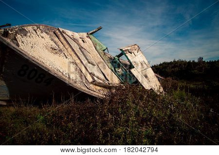 Old rotting wooden boat in a field in Prince Edward Island