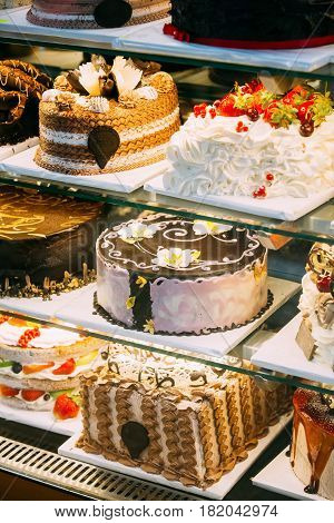Various Different Types Of Sweet Cakes In Pastry Shop Glass Display. Good Assortment Of Confectionery