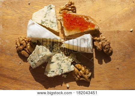 Different types of cheese, walnuts and caviar on wooden table