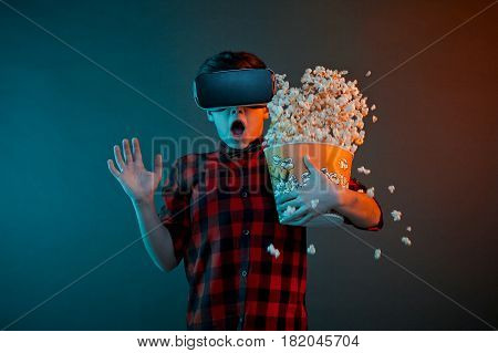 Little boy in VR headset looking scared and spilling popcorn on plain background.