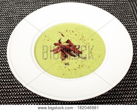 Homemade spicy broccoli cream soup with croutons in white bowl - healthy green vegetarian vegan detox diet homemade fresh soup food