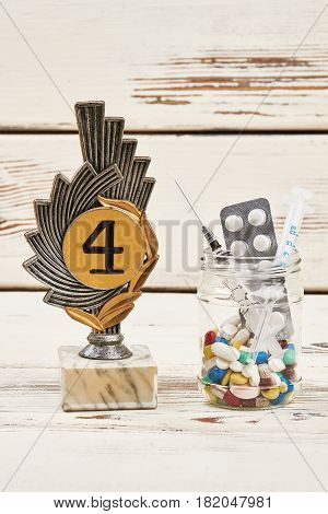 Pills and award on wood. Sport and doping dependence.