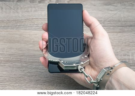 People Are In Hostages By Gadget. Man's Hand Attached With Handcuffs To Cell Phone, Mat Warm Toning.