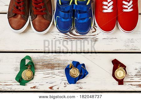 Multicoloured sneakers and medals. Steps to goal achievement.