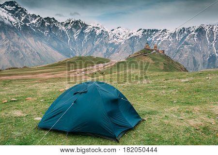 Kazbegi, Georgia. Tent Near Gergeti Trinity Church Or Tsminda Sameba - Holy Trinity Church. Travel And Hiking Concept