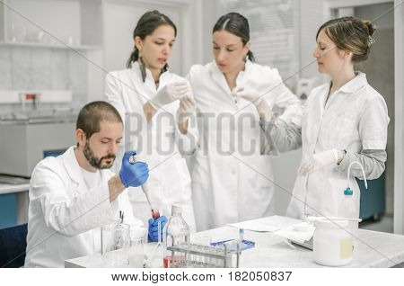Group Of Scientists Working With Liquid Test Tube Samples