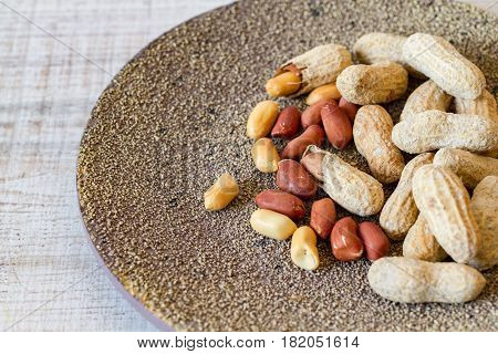 Raw peanuts or groundnuts on a plate, close up