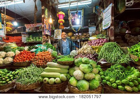 BANGALORE, INDIA - FEB 11, 2017: Vendor of zucchini cabbage greens and other vegetables waiting for customers at farmer market on February 11, 2017. Capital of state Karnataka has a popul. of 8.42 million