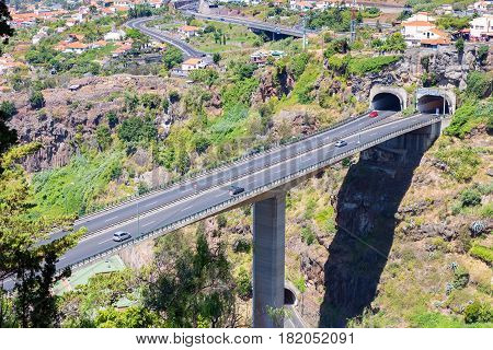 Cars driving on highway and overpass through tunnels at Madeira Portugal