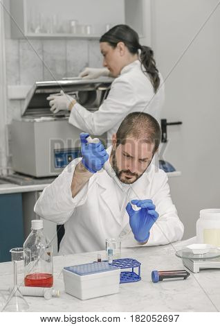 Two scientists in the laboratory filling test tubes with pipette. Close up