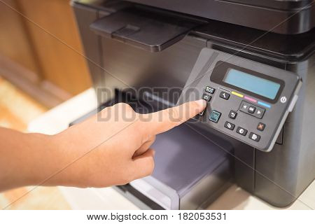 Copier Start Finger pressing the start button on a multifunction printer or copier