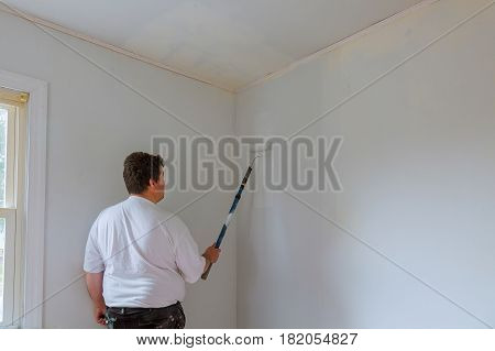 painter man at work with a paint roller and bucket wall painting concept paint roller wall painting