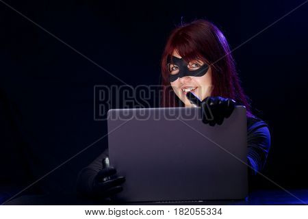 Thief in mask holds laptop