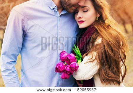 Romantic Love Story. Close-up Portrait Of Bearded Man Hugging His Lovely Girlfriend Holding Flowers.