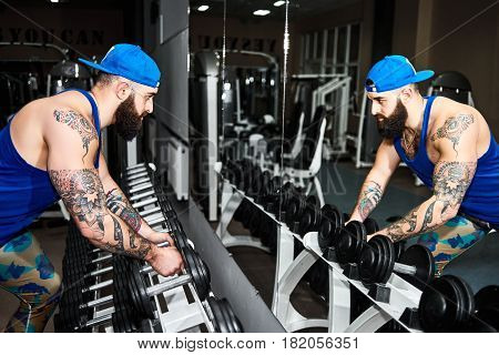 Young bearded tattooed man in baseball cap is standing in front of a mirror with dumbbells in his hands in the gym. Muscular young man exercising in front of mirror