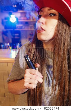 Young pretty woman in red cap smoke an electronic cigarette at the vape shop.