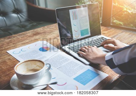 Closeup business woman hands using laptop with cup of coffee graph financial and network diagram documents on wooden table.