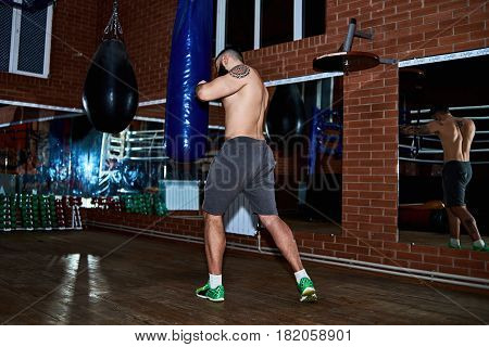 Young bearded tattooed man with naked torso hits a punching bag in the gym. Full body length portrait