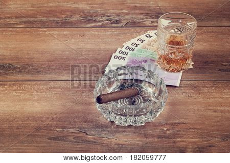 Glass of whiskey with cuban cigar on a brown wooden table. Top view.