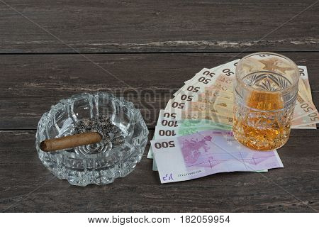 Glass of whiskey and a money with cuban cigar on a grey wooden table. Top view.