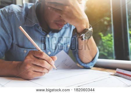 Stressed Asian Freelance designer. Close up man thinking about his job.