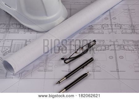 Burgas, Bulgaria - April 9, 2017: Architects workplace - architectural blueprints with measuring tape, safety helmet, glasses and propelling pencil on table. Top view.
